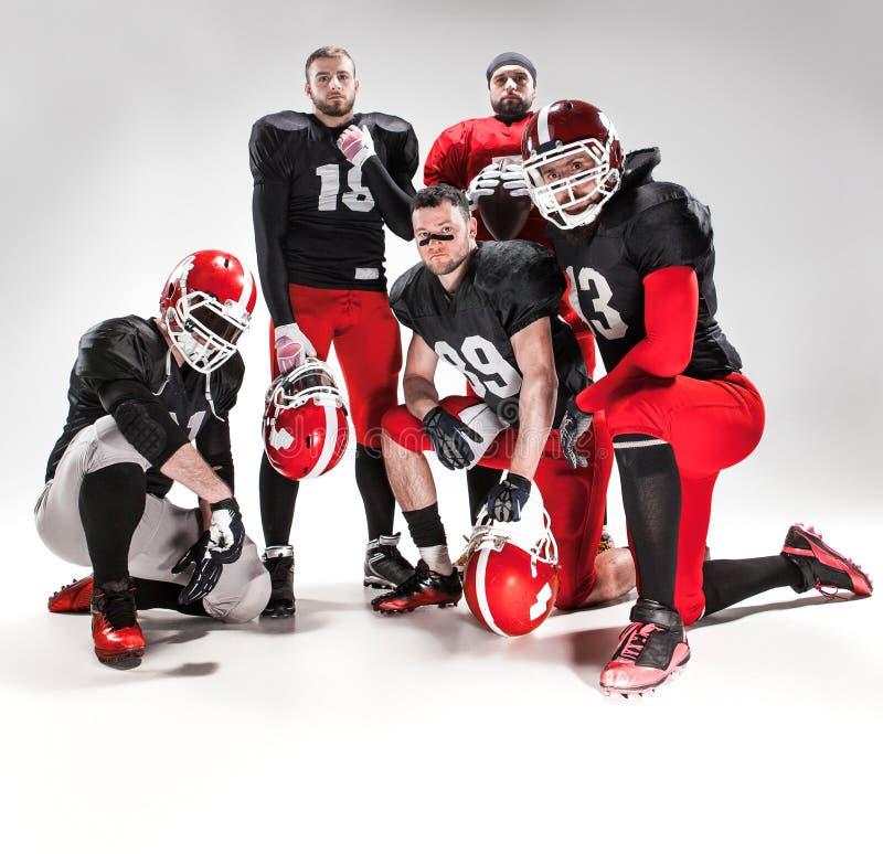 Pięć futbol amerykański graczów pozuje z piłką na białym tle fotografia royalty free