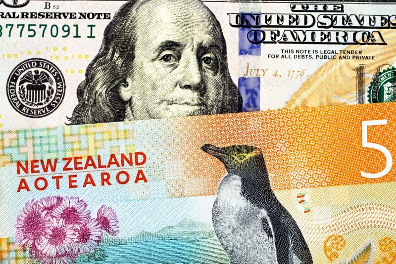 Pięć Nowa Zelandia dolarowy rachunek zamknięty w górę Amerykańskich sto dolarowych rachunków z zdjęcie stock