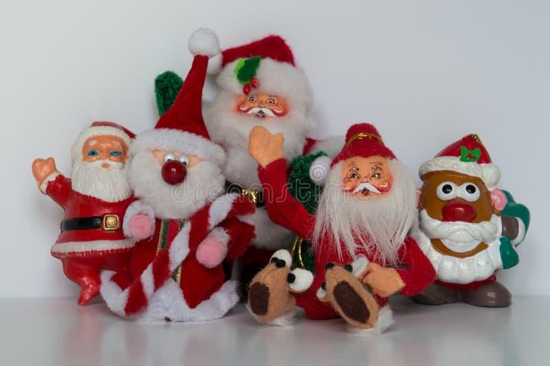 Pięć Santa ornamentów z cztery stoi i jeden sadzali, machający przy kamerą zdjęcie royalty free