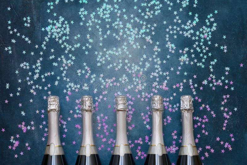 Pięć Szampańskich butelek z holograficznymi confetti grają główna rolę na błękitnym tle Odbitkowa przestrze?, odg?rny widok obrazy royalty free