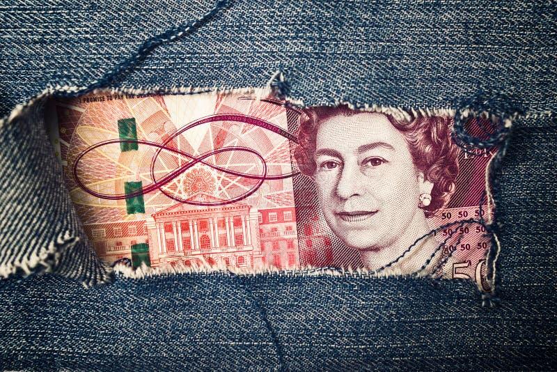 Pięćdziesiąt funtów rachunku przez poszarpanej niebiescy dżinsy tekstury zdjęcia stock