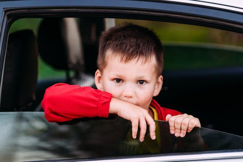 Pięcioletni dziecka obsiadanie w samochodzie i spojrzenia z otwartego okno obrazy royalty free