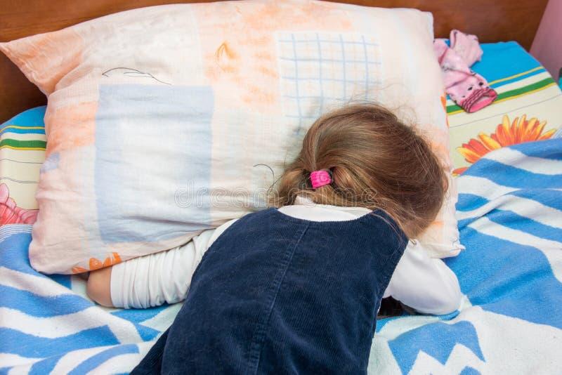 Pięcioletni dziewczyna płacz z jego twarzą zakopującą w poduszce zdjęcia stock