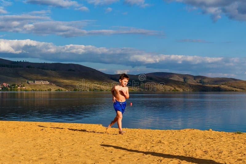 Pięcioletnia chłopiec bez koszulowy działający bosego na żółtym piasku na plaży w lecie, bezpośredni światło słoneczne obraz royalty free