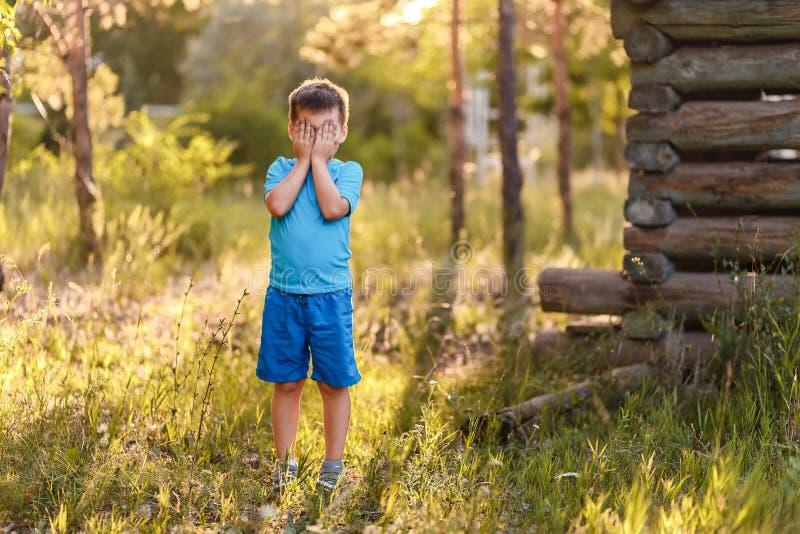 Pięcioletnia chłopiec w błękitów ubraniach zakrywa jego twarz z jego rękami w lecie w kontra zmierzchu światło obraz stock