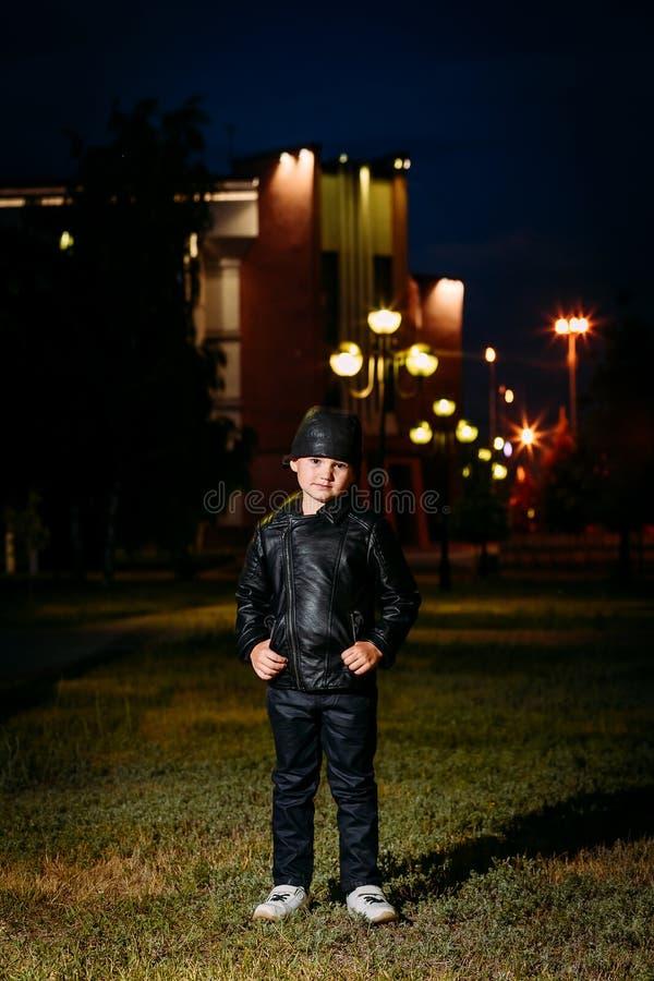 Pięcioletnia elegancka chłopiec w czarnej skórze i skórzanej kurtce dyszy na tle miasto przy nocą zdjęcie stock