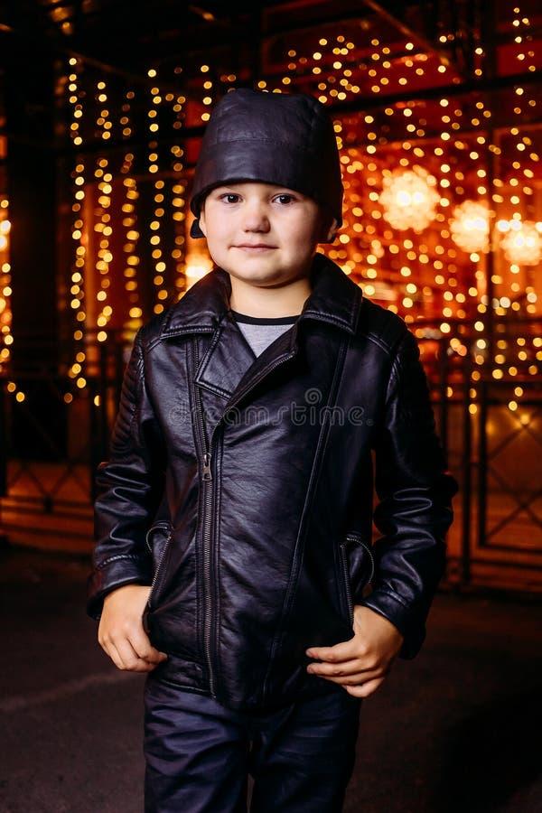 Pięcioletnia przystojna chłopiec w czerni skórzanej kurtki bandanach na tle nocy miasto zdjęcia royalty free