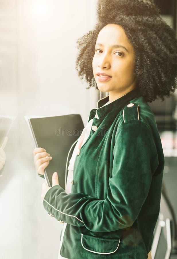 Piękna łacińska brazylijska dziewczyny pozycja obok okno i mienia notatnika fotografia royalty free