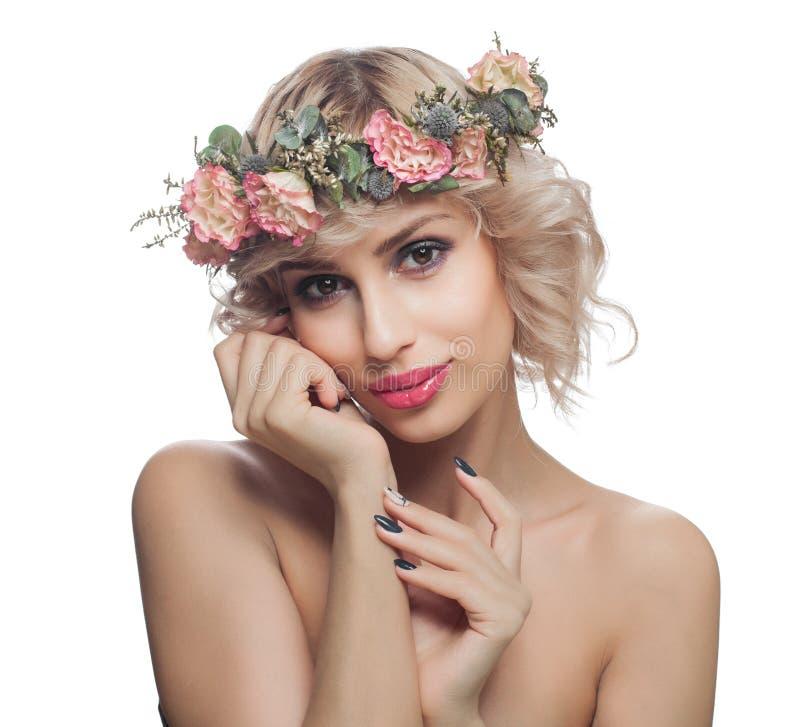 Piękna ładna kobieta z wiosna kwiatami Modeluje z makeup i blondynka kędzierzawym włosy odizolowywającymi na bielu zdjęcie stock
