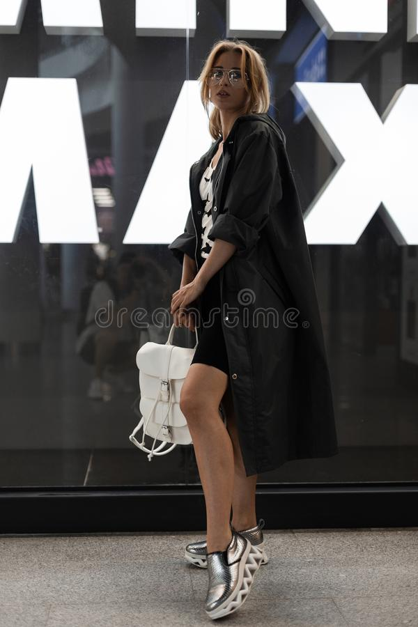Piękna ładna młoda kobieta w modnych ubraniach w szkłach z białej skóry plecakiem w srebrze kuje pozować indoors fotografia stock