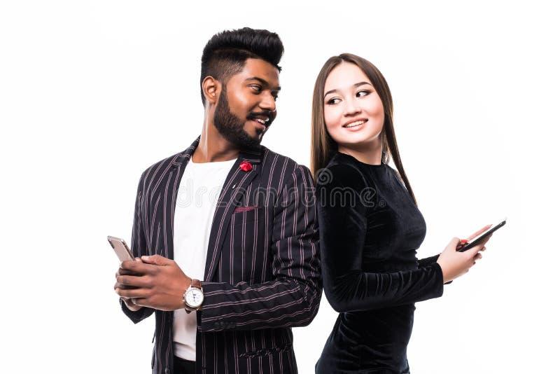 Piękna, ładna, urocza azjatycka kobieta i przystojny indiański mężczyzna stojący z powrotem na plecach i piszący sms przez 3g int obraz stock