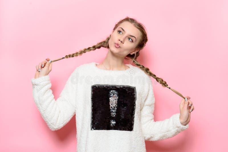 Piękna śliczna dziewczyna ma zabawę i trzyma pigtails pozuje blisko menchii ściany zdjęcia royalty free