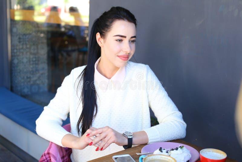 Piękna śliczna dziewczyna szczebiocze, plotkujący z przyjaciółmi w kawiarni obraz stock