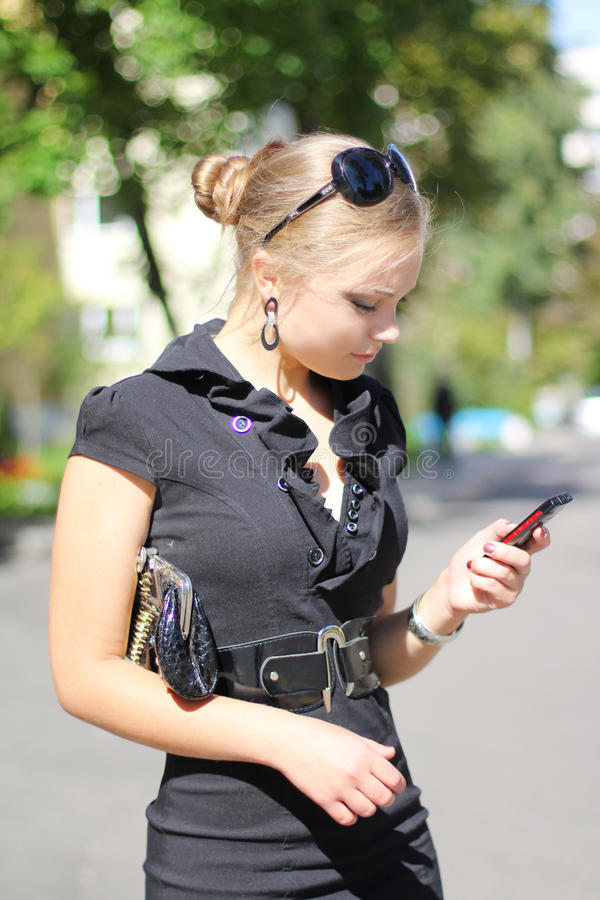 Piękna śliczna dziewczyna w czarnej sukni z telefonem obrazy stock