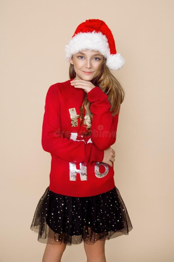 Piękna, śliczna mała dziewczynka, będący ubranym czerwonego Bożenarodzeniowego pulower i czerwoną nakrętkę Święty Mikołaj obraz stock