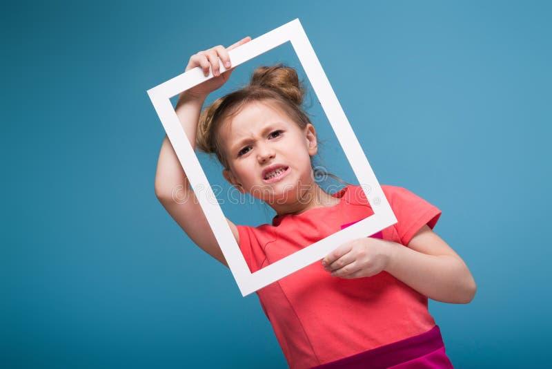 Piękna śliczna mała dziewczynka w menchii sukni trzyma obrazek ramę zdjęcia royalty free