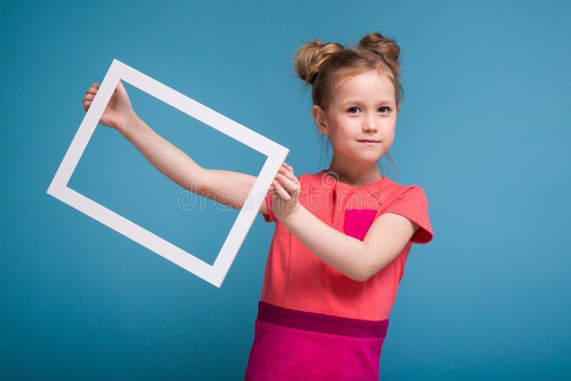 Piękna śliczna mała dziewczynka w menchii sukni trzyma obrazek ramę obrazy royalty free