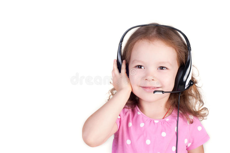 Piękna śliczna szczęśliwa mała dziewczynka z hełmofonami zdjęcie stock