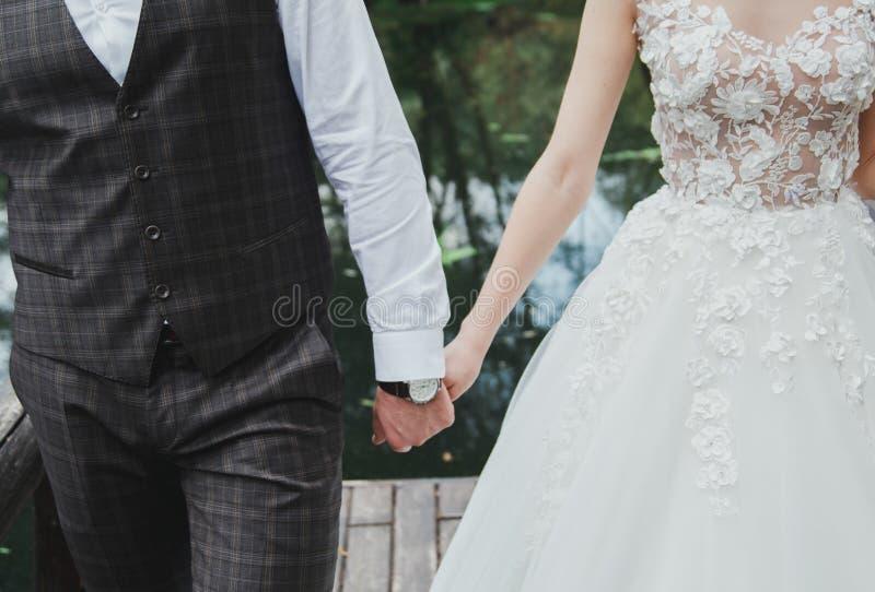 Piękna ślub para stoi na drewnianym moście Panna młoda w białych kwiatów sukni trzyma ręki brodate z ona obrazy royalty free
