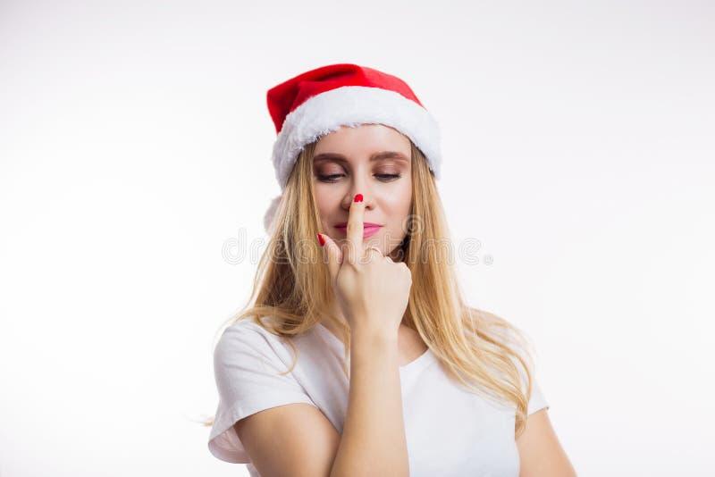 Piękna śmieszna blondynki kobieta jest ubranym czerwony Santa kapeluszowy ono uśmiecha się i palec wskazuje przy jej nosem na bia zdjęcia royalty free