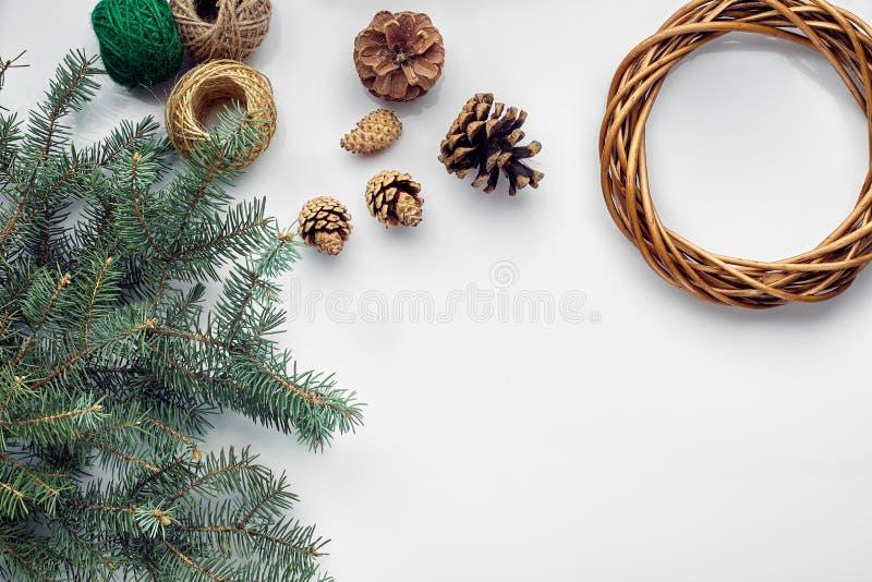 Piękna świąteczna handmade wianek baza z trzy garbkami blisko go, nici i gałązki błękitnej choinki na bielu, obraz stock
