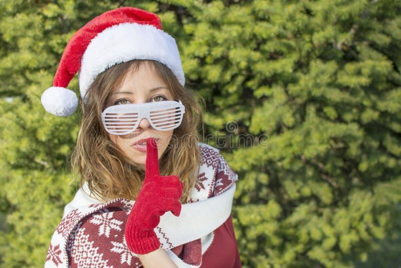 Piękna Święty Mikołaj dziewczyna z palcem na jej wargach zdjęcie stock