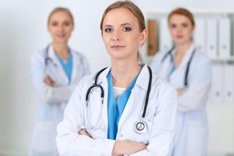 Piękna żeńska lekarz medycyny pozycja przy szpitalem przed medyczną grupą Lekarz przygotowywa pomagać pacjenta zdjęcia royalty free
