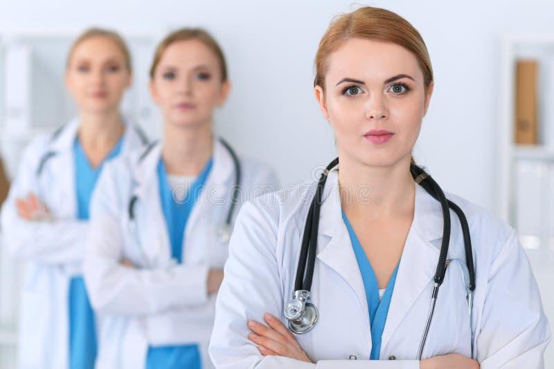 Piękna żeńska lekarz medycyny pozycja przy szpitalem przed medyczną grupą Lekarz przygotowywa pomagać pacjenta fotografia royalty free