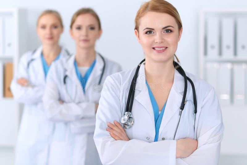 Piękna żeńska lekarz medycyny pozycja przy szpitalem przed medyczną grupą Lekarz przygotowywa pomagać pacjenta fotografia stock