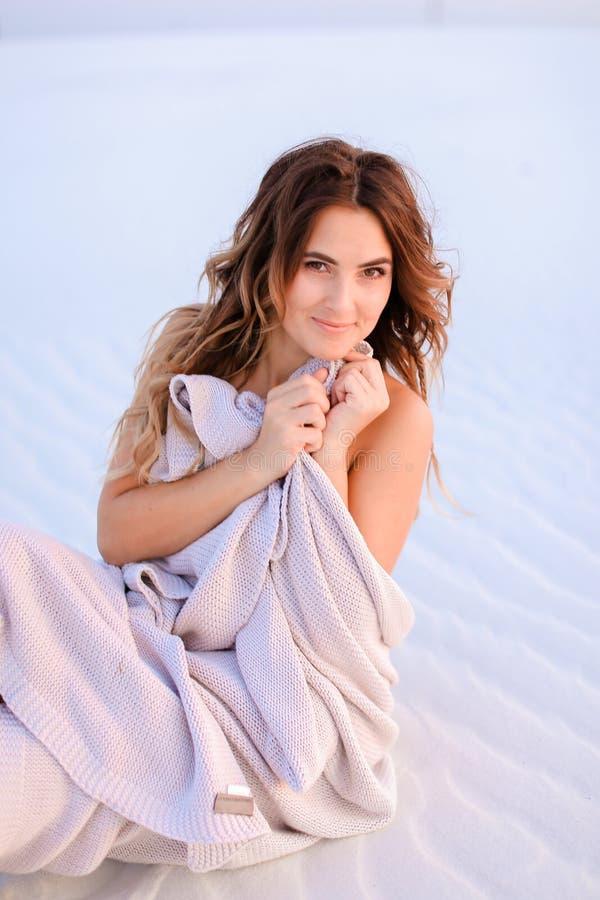 Piękna żeńska osoba zawijająca w powszechnym obsiadaniu na białym piasku zdjęcie royalty free