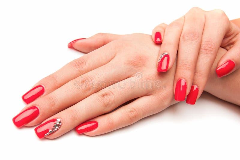 Piękna żeńska ręka z czerwień gwoździami odizolowywającymi na bielu obrazy royalty free
