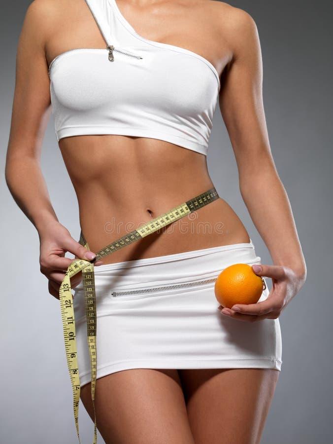 Piękna żeński ciało z pomiarową taśmą i pomarańcze zdjęcie royalty free