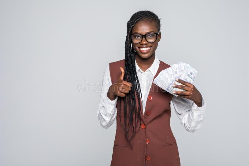 Piękna Afroamerykańska kobieta trzyma rękę gotówkowy pełno i daje aprobata znakowi odizolowywał szarego tło fotografia stock