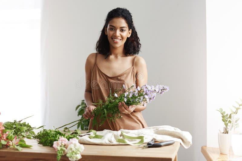 Piękna afrykańska żeńska kwiaciarnia ono uśmiecha się patrzejący kamery mienia kwitnie biała ściana Właściciel biznesu szczęśliwy zdjęcie royalty free