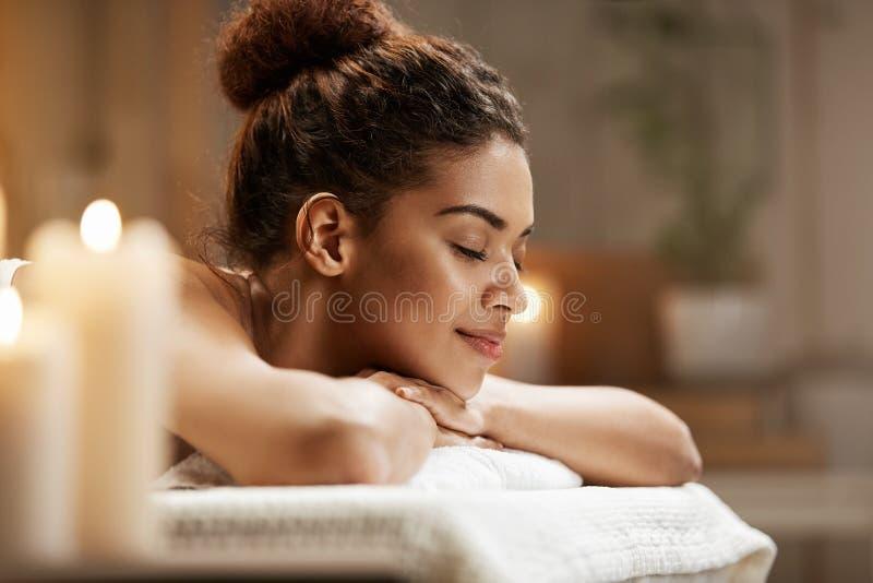 Piękna afrykańska dziewczyna odpoczywa relaksować w zdroju kurorcie z zamkniętymi oczami zdjęcia stock