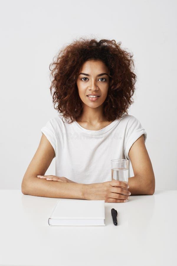 Piękna afrykańska dziewczyna ono uśmiecha się patrzejący kamery obsiadanie przy stołem nad białym tłem obrazy stock