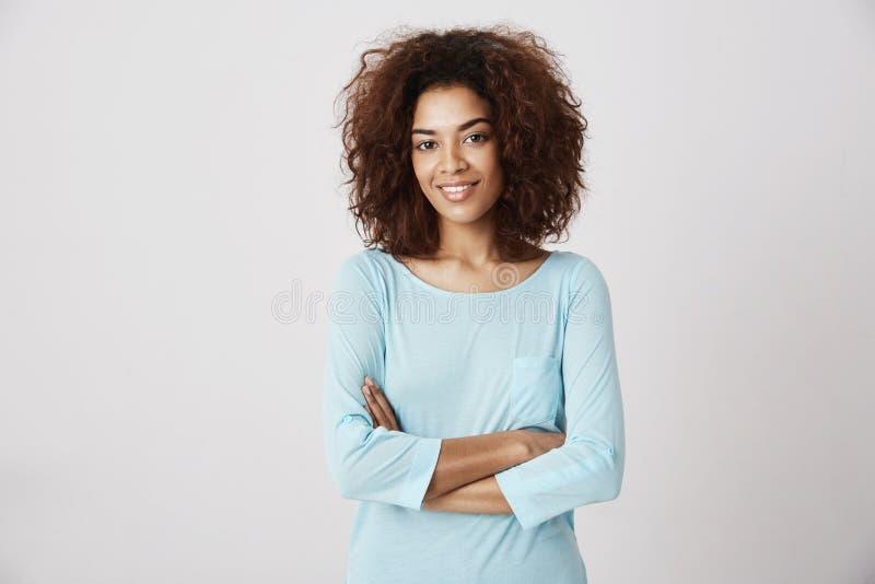 Piękna afrykańska dziewczyna uśmiecha się pozować z krzyżować rękami fotografia royalty free