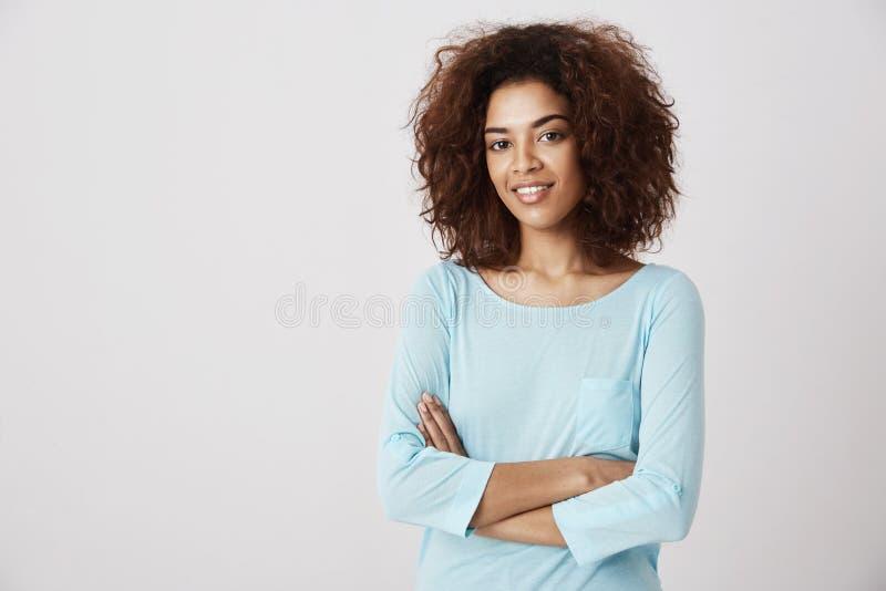 Piękna afrykańska dziewczyna uśmiecha się pozować z krzyżować rękami nad białym tłem kosmos kopii zdjęcia royalty free