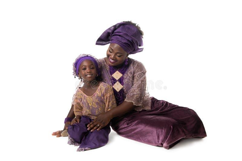 Piękna Afrykańska kobieta i urocza mała dziewczynka w taditional ubieramy odosobniony obraz stock