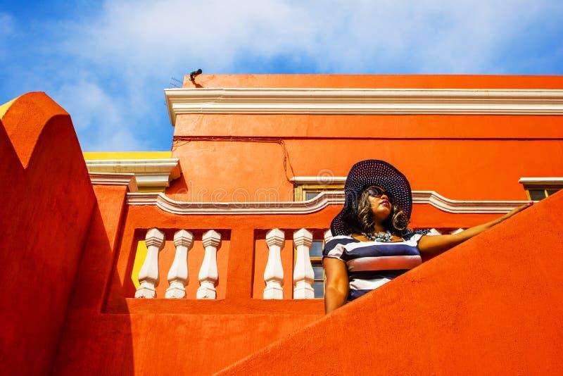 Piękna Afrykańska kobieta w błękitnej i białej pasiastej smokingowej modelacji przed tradycyjnym bo stwarza ognisko domowe z poma obrazy stock