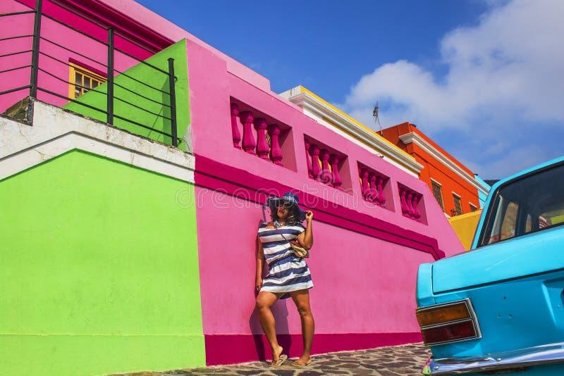 Piękna Afrykańska kobieta w bielu i błękitnym paskował smokingowy zwiedzać w tradycyjnych domach bo i wokoło, Kapsztad zdjęcia royalty free