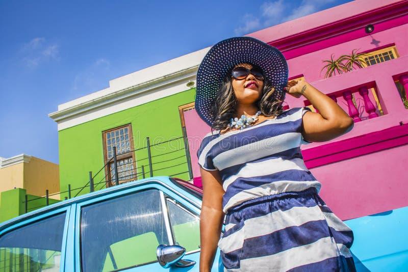 Piękna Afrykańska kobieta w bielu i błękitnym paskował suknię przed rocznika Ford Cortina tradycyjnymi domami bo i, C zdjęcie stock