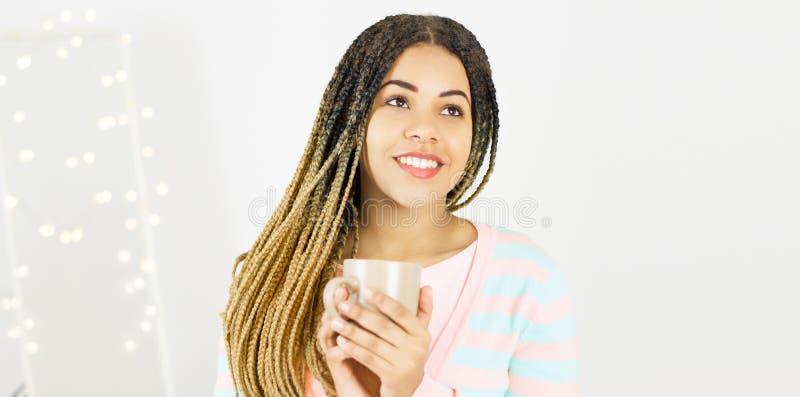 Piękna amerykanin afrykańskiego pochodzenia dziewczyna z filiżanką i afro fryzury ono uśmiecha się obraz stock