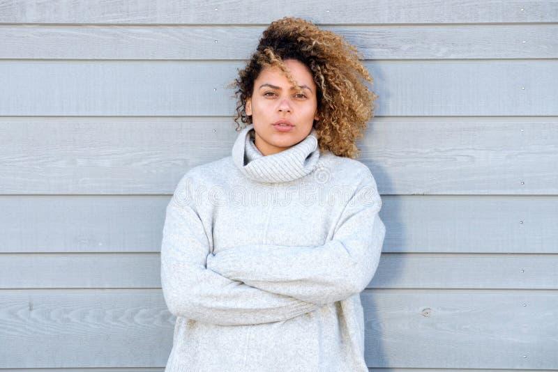Piękna amerykanin afrykańskiego pochodzenia kobieta w ciepłym pulowerze z rękami krzyżować obrazy royalty free