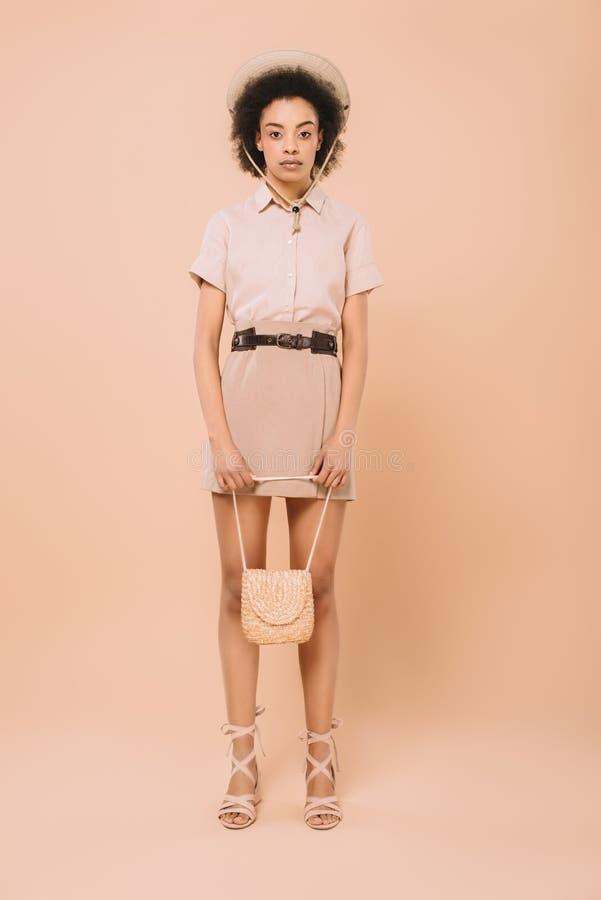 piękna amerykanin afrykańskiego pochodzenia kobieta w eleganckiej odzieży z torbą fotografia stock