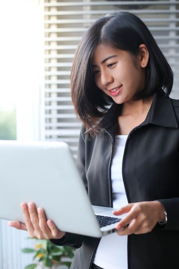 Piękna Asia biznesowa kobieta uśmiecha się laptop z i trzyma zdjęcie stock