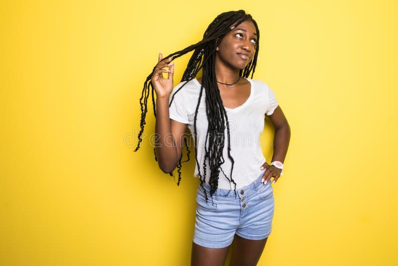 Piękna atrakcyjna amerykanin afrykańskiego pochodzenia kobiety przeniesienia sztuka z jej kędzierzawym afro włosy na Żółtym praco obrazy royalty free