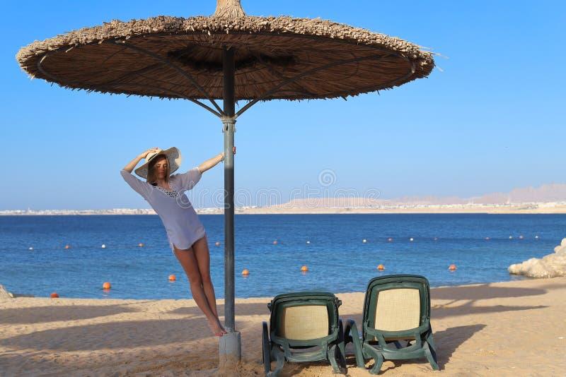 Piękna atrakcyjna dziewczyna w swimsuit z światło plaży sukni pozycją na słonecznym dniu pod słomianym parasolem i obraz stock