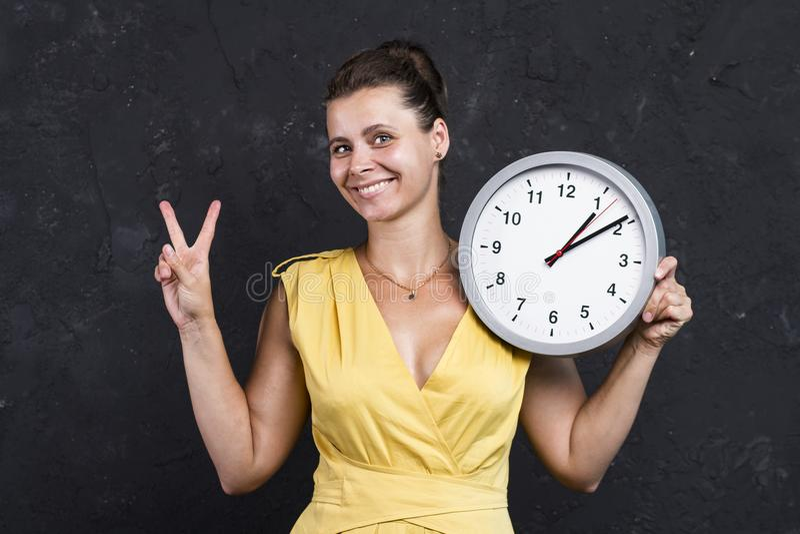 Piękna atrakcyjna dziewczyna z zegarem Młoda kobieta trzyma round zegarek tła pojęcia odosobniony przedmiota czas biel fotografia royalty free