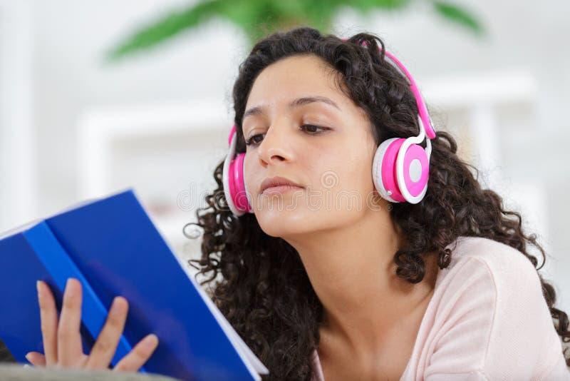 Pi?kna atrakcyjna kobieta czytaj?ca s?ucha muzyk? podczas gdy zdjęcie royalty free
